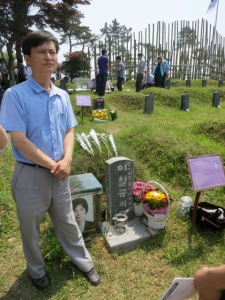 Lee Shin, activist, stands beside the grave of a man tortured to death for writing a book exposing the truth about the Gwangju uprising, a man from who he draws personal strength.